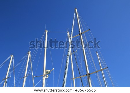 Sail boat masts against a dark blue sky