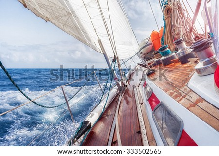 sail boat navigating on the waves - stock photo