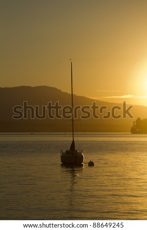 Sail boat on a mountain lake during sunset