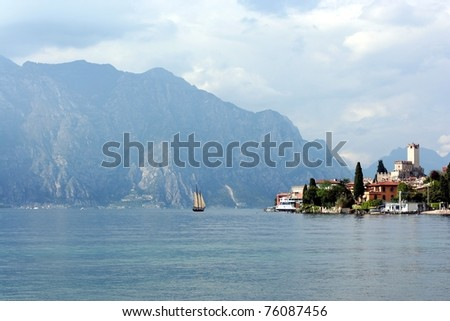 Sail boat on morning Lago di Garda lake near resort Malcesine with mountains as a background - stock photo
