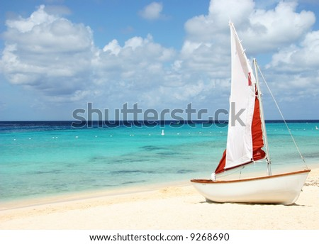 Sail boat on tropical beach with blue water background - stock photo