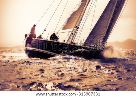 sail boat sailing on sunset - stock photo