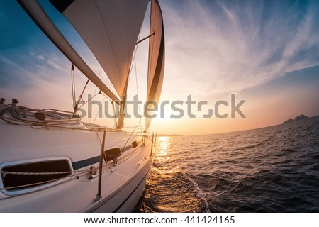 Sail boat with set up sails gliding in open sea at sunset - stock photo