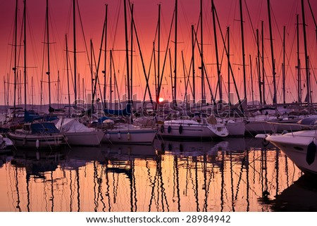 sail boats in harbour with sundown - stock photo