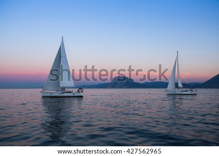 Sail boats near the rocky shores after amazing sunset. - stock photo