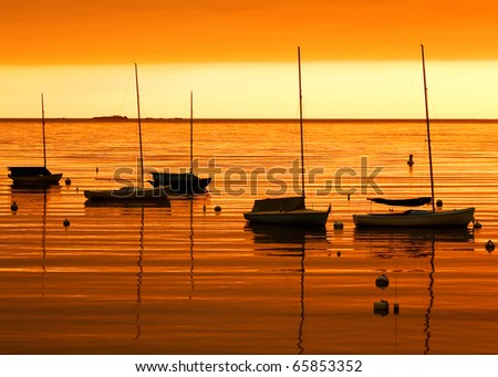 Sail boats tied up in port as the sun colors everything orange during twililght. - stock photo