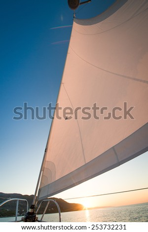 Sail of a sailing boat against sunset - stock photo