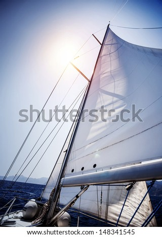 Sail of the yacht fluttering in the wind, summer adventure, sea cruise on sailboat, yachting sport, active lifestyle, holidays and vacation concept - stock photo