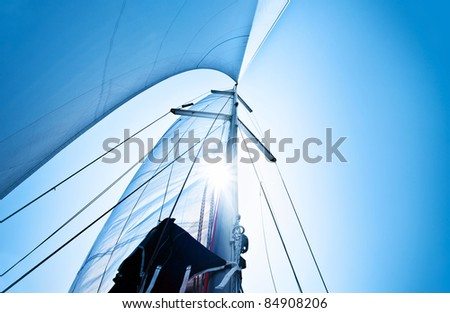 Sail over clear blue sky, sailboat over natural background with sunlight, summertime activities and extreme sport - stock photo