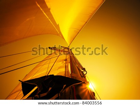 Sail over warm yellow sunset sky, sailboat over natural background - stock photo