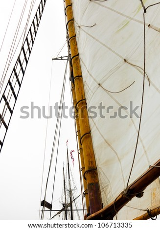 Sail, rigging and mast of a classic wooden sailboat, with a tall ship in the background.  Looking up from the deck.