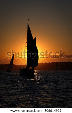 Sail ship at the sunset on the ocean. - stock photo