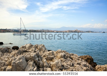 sailboat anchored at the bay of Antibes, rocks in foreground
