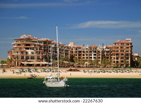Sailboat Anchored in Front of A Beach Resort - stock photo