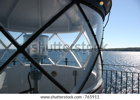 Sailboat and ocean view through harbor light glass. - stock photo