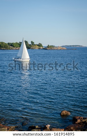 Sailboat and rocky coastline in nice clean sea - stock photo