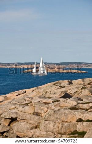 Sailboat and rocky coastline in sea archipelago - stock photo