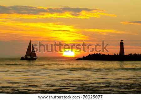 Sailboat and Silhouette Lighthouse with sunset in the background - stock photo