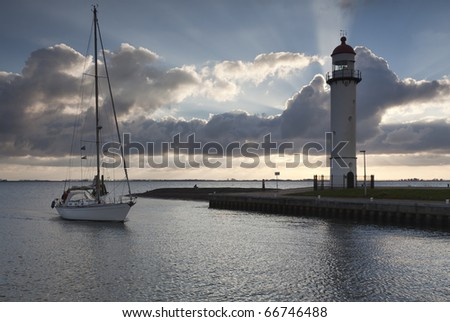 Sailboat approaching harbor jetty with lighthouse at sunset - stock photo