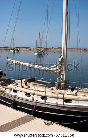 Sailboat at dock on clear day with blue sky background - stock photo