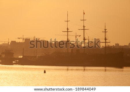 Sailboat at Mytninskaya embankment in St. Petersburg, Russia. The view at sunset.
