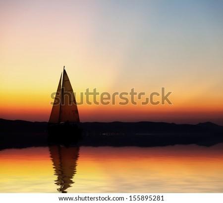Sailboat at sunset  - stock photo
