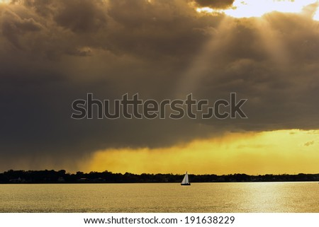 Sailboat at sunset on the Chesapeake Bay with a stormy sky - stock photo