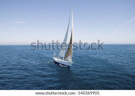Sailboat at the peaceful blue ocean against the sky - stock photo