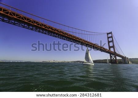 Sailboat beneath the  Golden Gate Bridge - stock photo