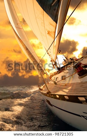 Sailboat crop during the regatta at sunset ocean - stock photo