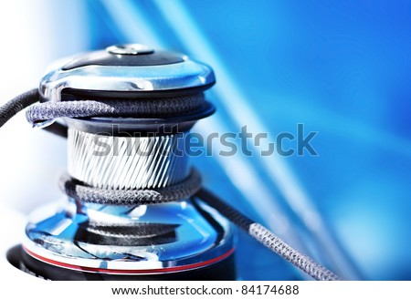 Sailboat detailed parts, close up on winch and rope of yacht over blue sea, shallow depth of field - stock photo