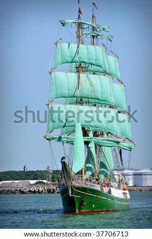 sailboat going out of port with full sails up - stock photo