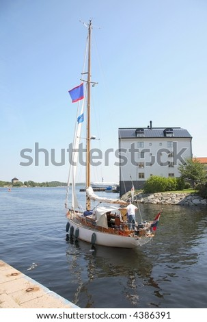 Sailboat, handled by one man, is leaving harbor in the tourist season. Karlskrona, Sweden. - stock photo