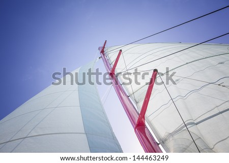 Sailboat in action, big white sail raised over blue clear sky
