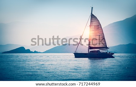 Sailboat in the sea in the evening sunlight over beautiful big mountains background, luxury summer adventure, active vacation in Mediterranean sea, Turkey