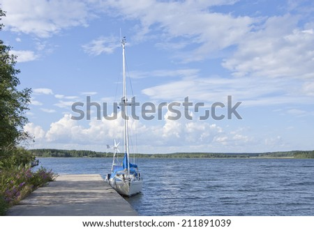 Sailboat moored by a bridge. Sunny day up North along the Baltic Sea. Blue sky, some clouds and forest in the background. - stock photo
