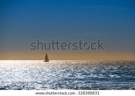 Sailboat navigates at sunset - stock photo