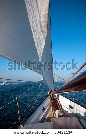 Sailboat navigates in the ocean while a boat is passing by. - stock photo