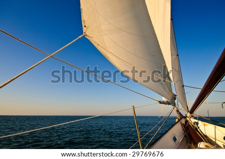 Sailboat navigating towards sunset in the caribbean. - stock photo