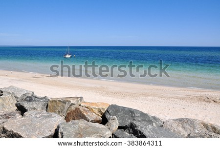 Sailboat off the Busselton Beach in the Indian Ocean with rocky breakwater detail/Sailing: Busselton Beach/Indian Ocean, Western Australia. - stock photo