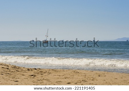 Sailboat off the coast of California with oil rigs in background - stock photo