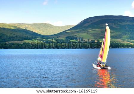 sailboat on a Scottish lake, beautiful hills in background - stock photo