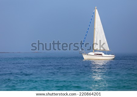 Sailboat on calm sea under a sunny summer day - stock photo