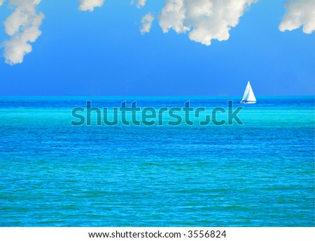 Sailboat on Emerald Sea Under Puffy Clouds