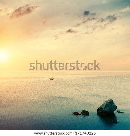 sailboat on horizon at sunrise time and stones in sea water - stock photo