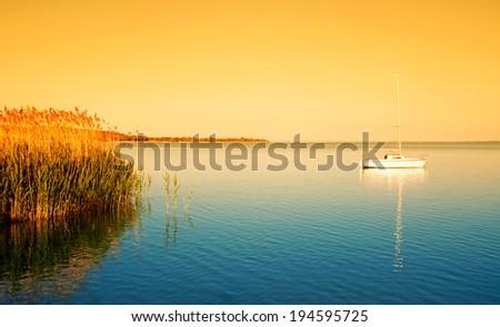 Sailboat on Lake Balaton in sunrise - stock photo
