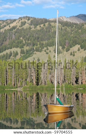 Sailboat on mountain lake - stock photo