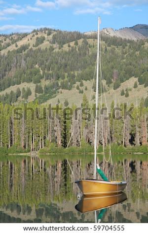 Sailboat on mountain lake - stock photo