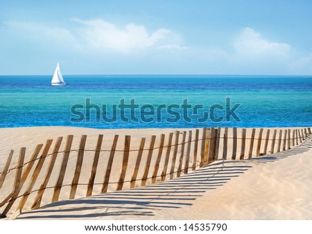 Sailboat on pretty sea with sand dune fence in foreground - stock photo
