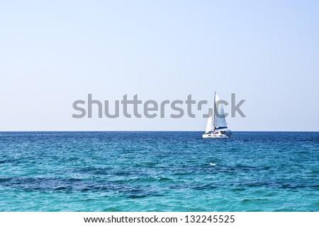 sailboat on the horizon on a sunny day - stock photo